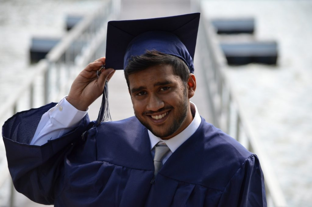 A student in his graduation gown holding his graduation hat.
