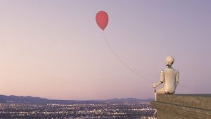 A white robot is sitting on the rooftop ledge of a building with the view of a city with lights, holding a red balloon.