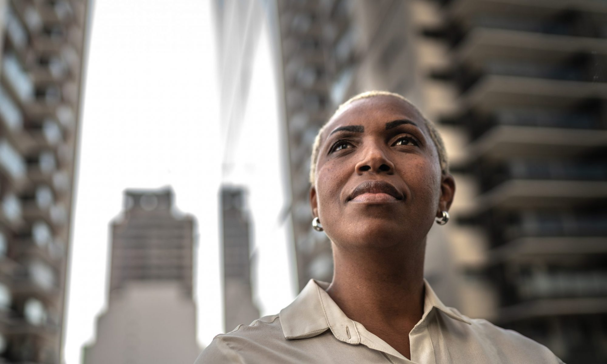 Here is a person with short blonde hair and dark skin wearing small hooped earing looking upwards with curiosity. This individual is wearing a silky sand coloured shirt with an unbuttoned collar.