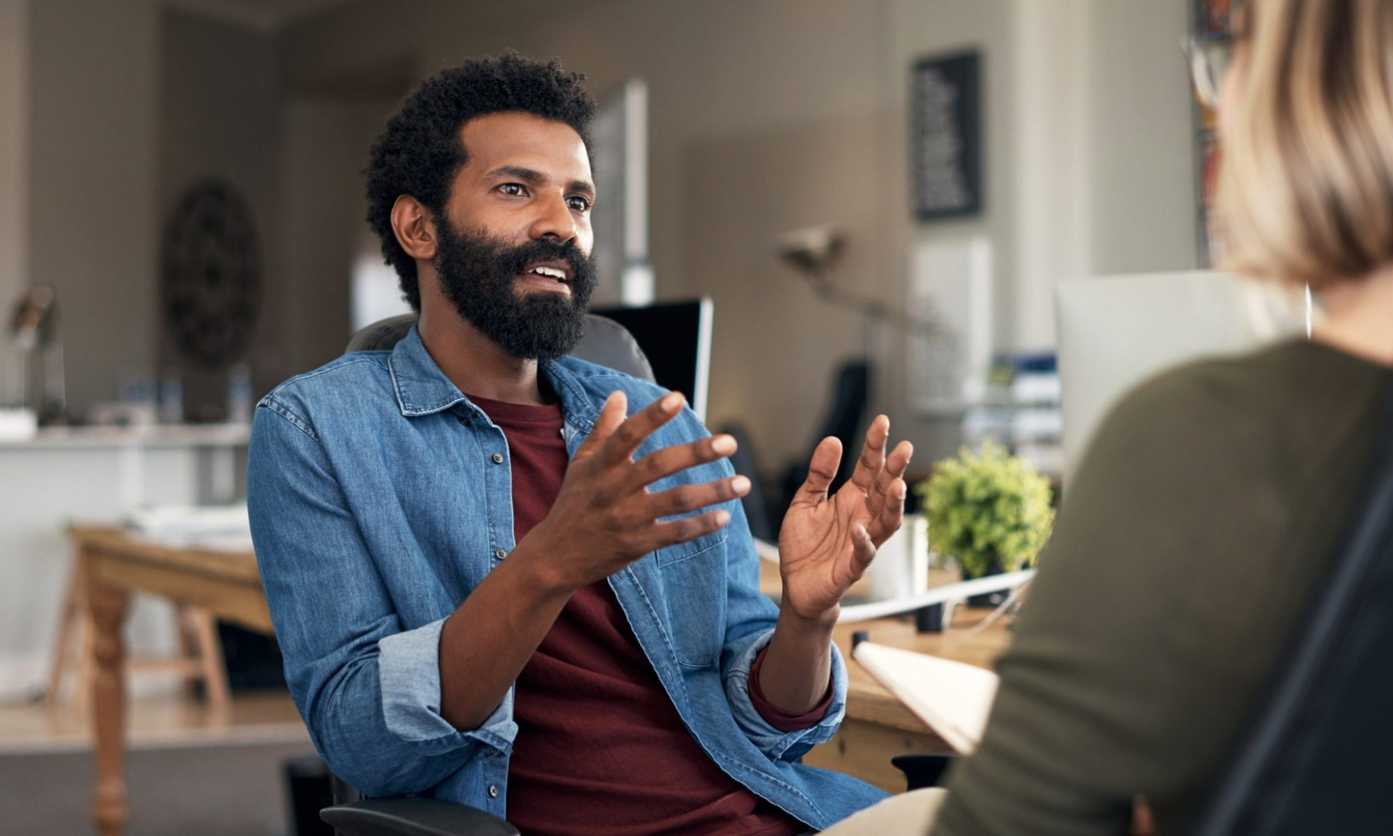 Here are two casually dressed individuals in a closed meeting in a creative office environment. The individual has short black afro hair with a black beard dressed in a maroon tee shirt and a denim long-sleeved on top.