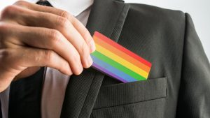 Close up of a business professional putting pride colours, LGBT+ card into the chest pocket of a smart black blazer.