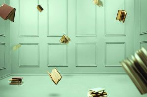 Here are multiple falling books in a closed pale green room.