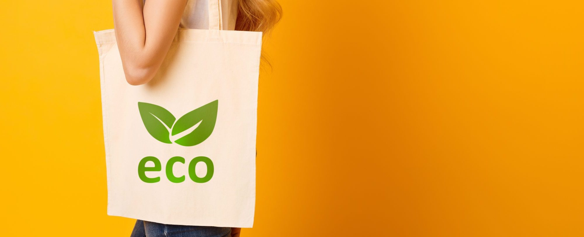 A person is carrying an eco-friendly fabric shopping bag with a green leaf logo stating 'eco'. The person is standing behind a bright solid orange background.
