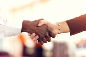 Two diverse hands are shaking. One hand has a long white sleeve, and the other has a silver bracelet with a black shirt sleeve—Symoblic to partnerships and diversity.