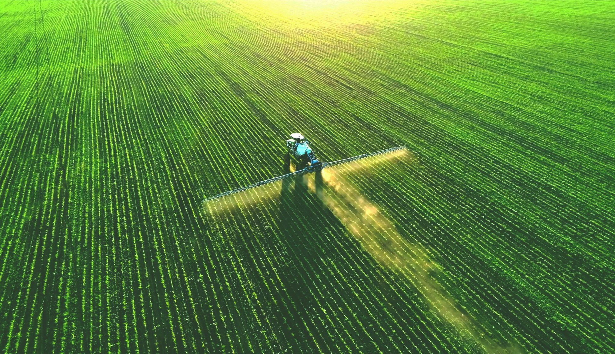 A tractor watering crops with a sprinkler system on a sunny day. This is symbolic to agricultural production.