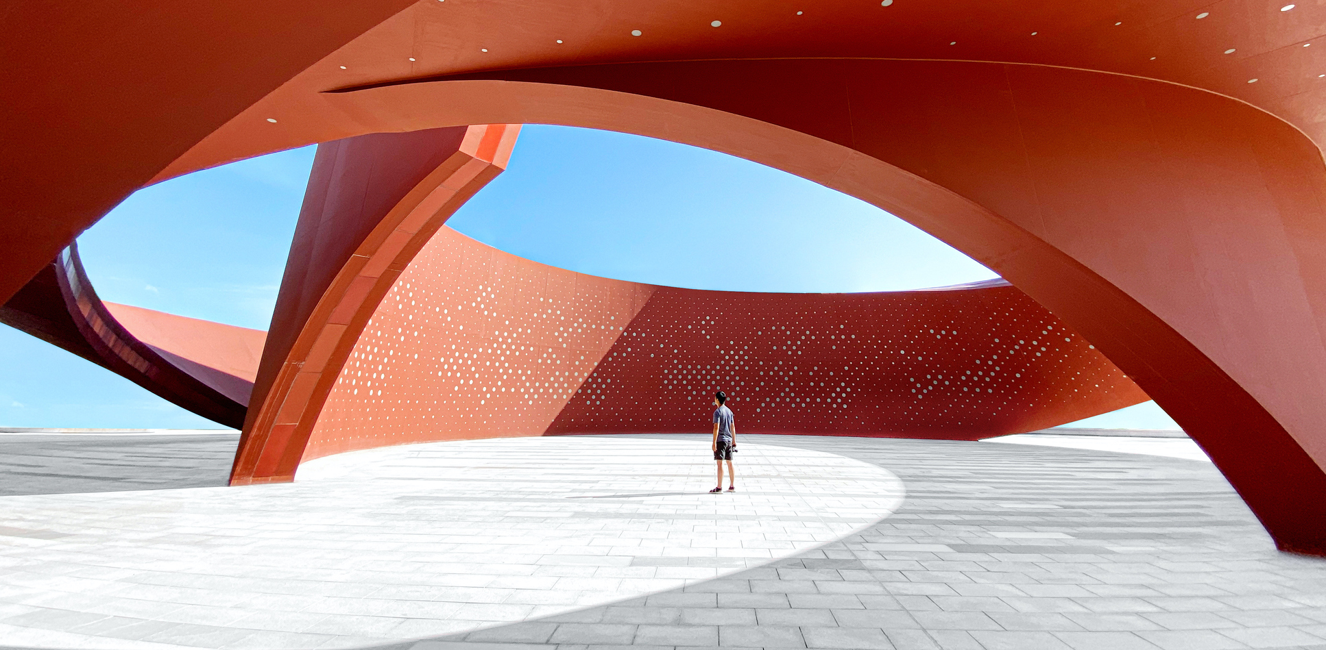 A person standing in a red curved abstract architectural space, 3D rendering