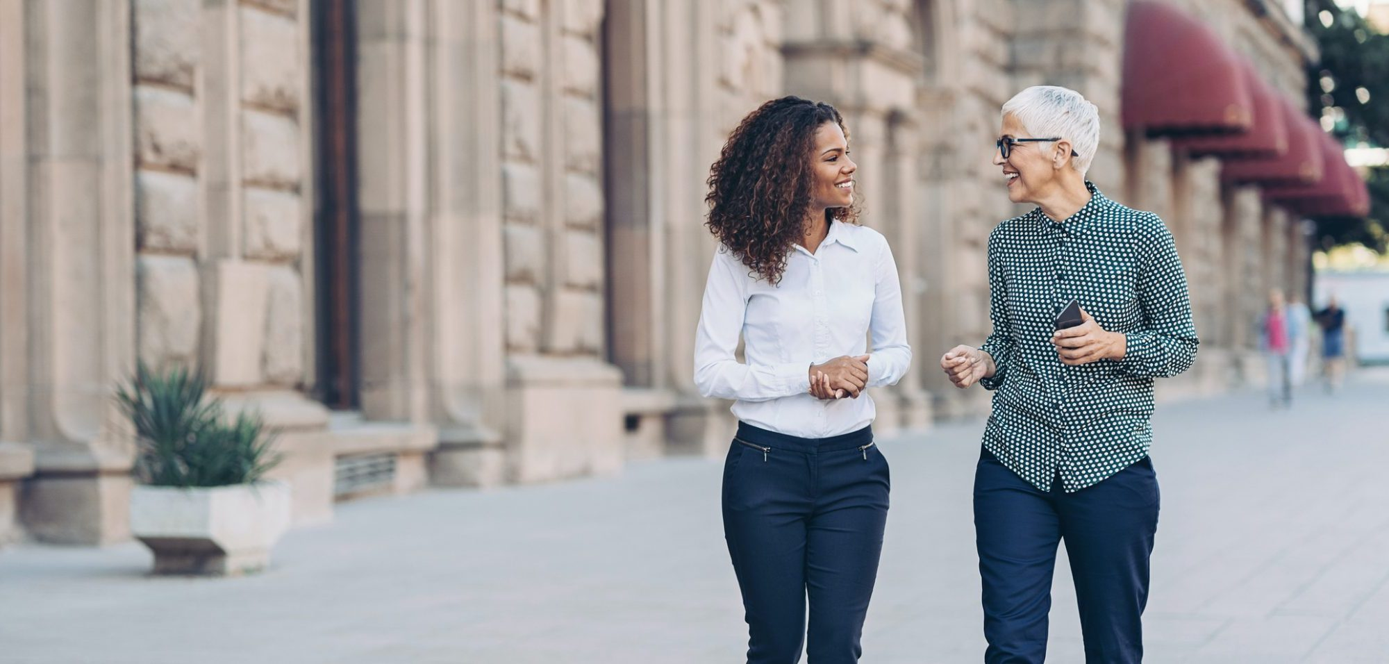 Here are two female business professionals engaged in a conversation and walking outside down a path.