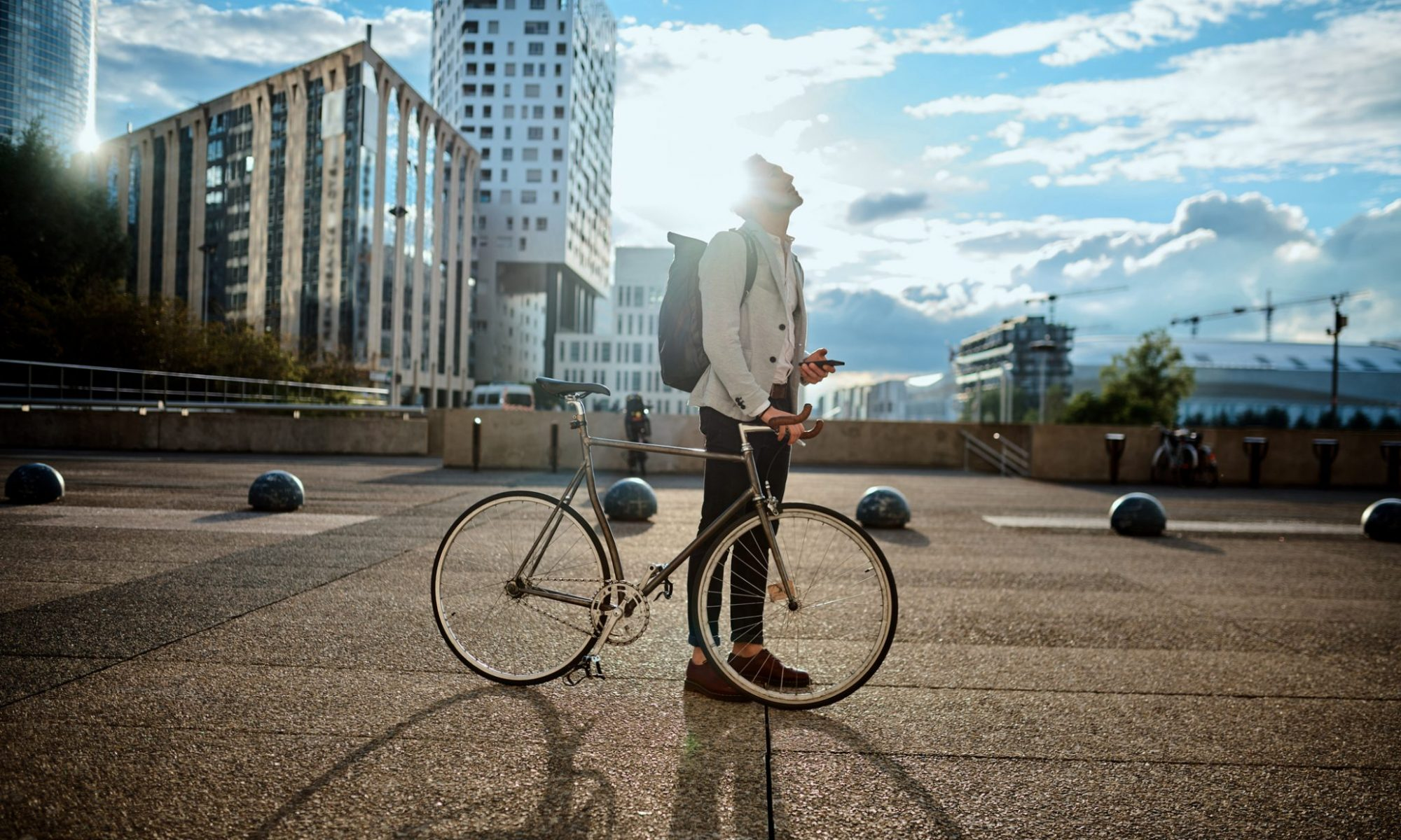 A student is looking into the bright blue sunny sky with a backpack on his shoulders, holding a mobile in one hand and resting the other on a bike. The student is in the city with high glassed buildings.