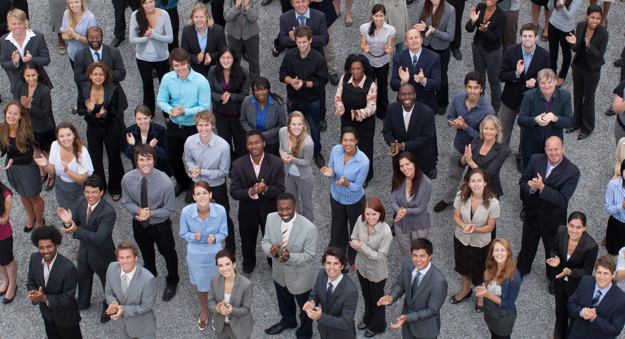 Here is a large, diverse crowd of business working professionals socially distancing standing outside dressed in smart attire.