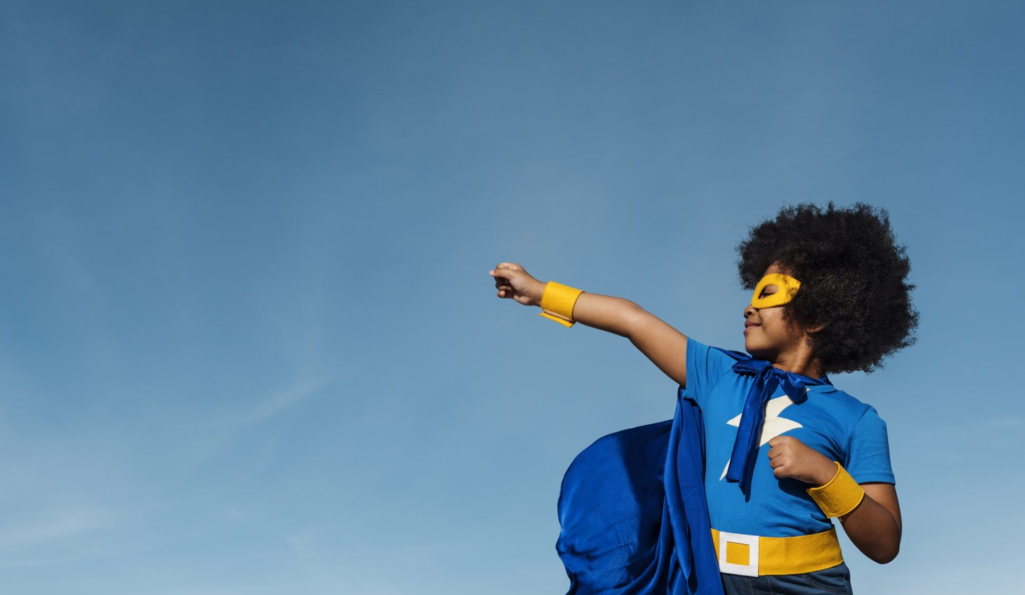 A kid with short black afro hair punching into the sky. The young kid is in a blue and gold superhero outfit with a mask, cap and a lightning bolt icon on his t-shirt. This is to symbolise transformation and impact.