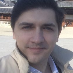 The Online Programme Director of the Center for Innovative Programs and Projects, IBS RANEPA, is smiling outside a brown building. The Online Programme Director has brown hair and blue eyes wearing a smart white shirt with the collar button undone, underneath a patterned blazer with a cream coloured coat with the collar flicked upright.