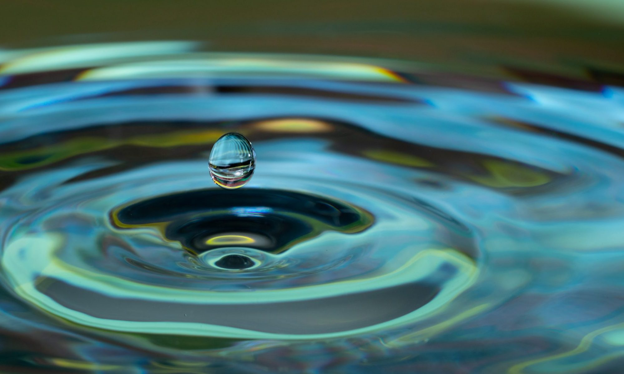 A close-up photograph of a single water droplet about to hit a pool of water; pool of water is causing a circular ripple motion. Water, in this case, signifies sustainability. Business Impact article for Making an impact: corporate social responsibility.