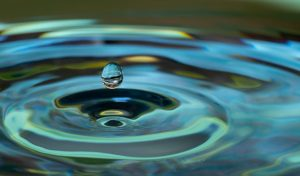 A close-up photograph of a single water droplet about to hit a pool of water; pool of water is causing a circular ripple motion. Water, in this case, signifies sustainability.
