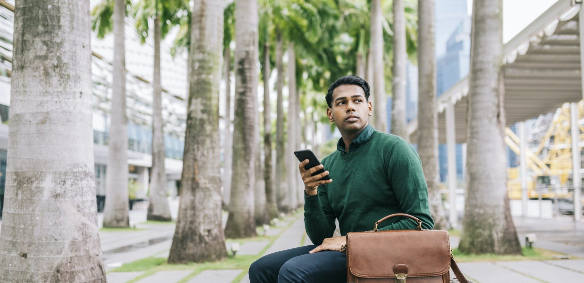 A future leader sitting on a bench outside holding his phone with his briefcase on the side.