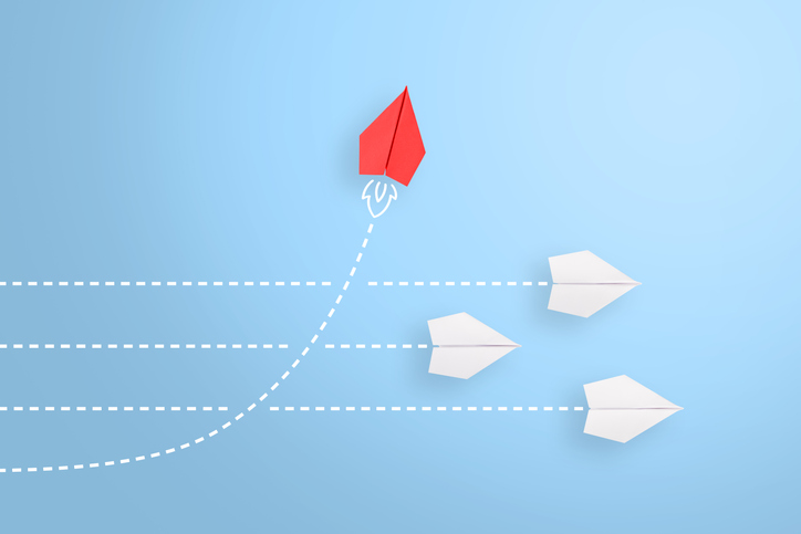 White paper plans heading in the same direction a red paper plain rocketing upwards. This is symbolic to navigating change.