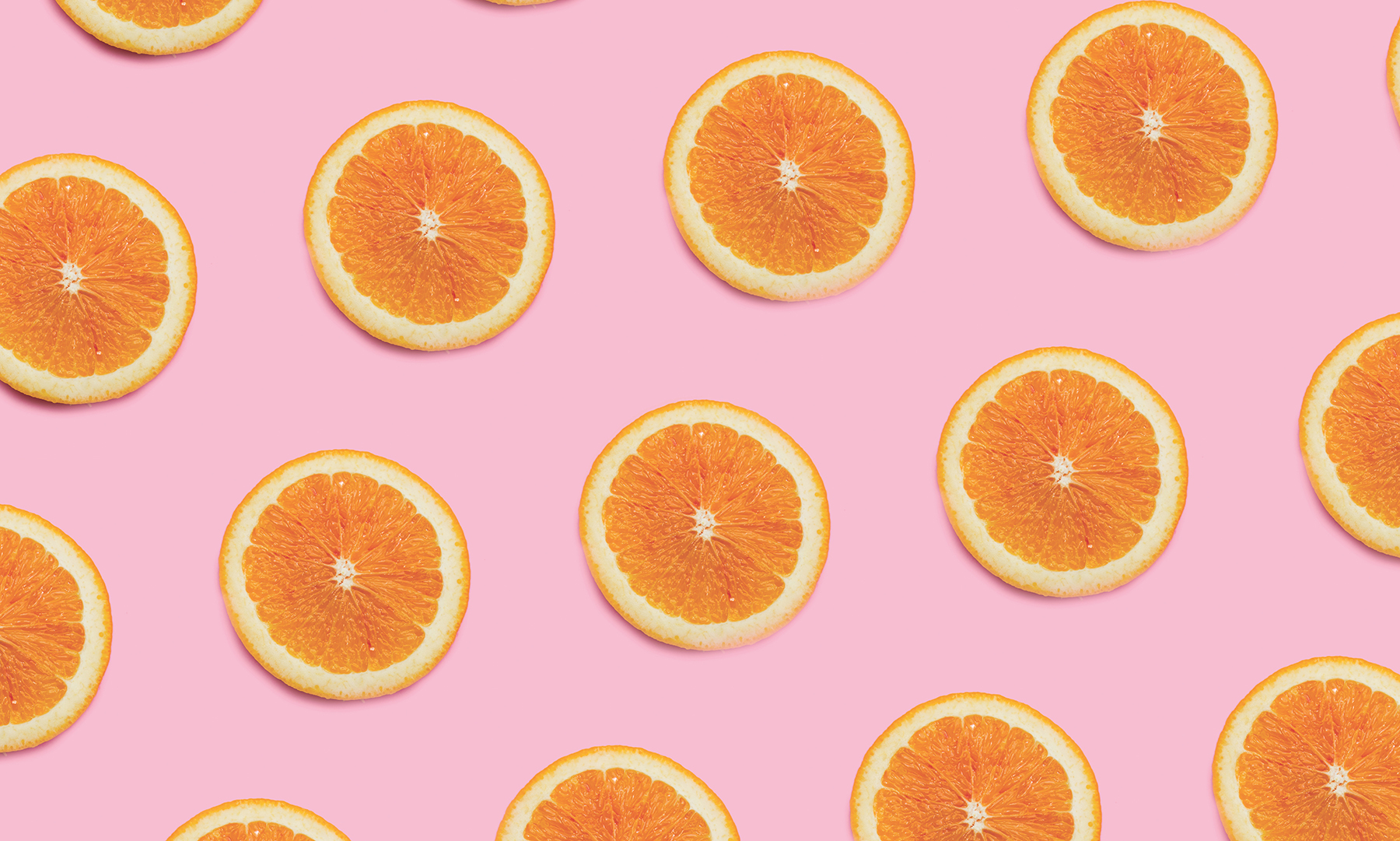 A fruitful pattern of cut oranges on a baby pink background.