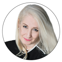 A headshot of the Director of Sustainability, Avon and the Judge of AMBA & BGA Excellence Awards smiling. The Director has white, straight long hair and blue eyes with peachy pink lipstick.