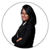 The CEO and Co-founder, Diversity & Inclusion Coach, BusinessWiz and Judge for AMBA & BGA Excellence Awards is smiling with her hands folded across her body. She has long black hair with brown eyes and bright red lipstick. Also, she is wearing a white top with a black blazer on top.