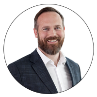 Director of Artificial Intelligence, Technology & Investments, PwC and Judge of the AMBA & BGA Excellence Awards grinning. The Director has brown hair, blue eyes with a thick, trimmed beard, and a white shirt with an unbuttoned collar and a checked grey-black blazer.