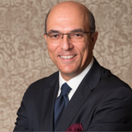 The Professor of Management, Dean of the School of Business at the American University in Cairo and speaker for AMBA & BGA Accreditation Forum, is grinning. The Dean wears clear oval glasses and is dressed in a smart white shirt, navy blue blazer, and a navy blue tie. The outfit is accompanied by a burgundy handkerchief emerging from the left pocket.